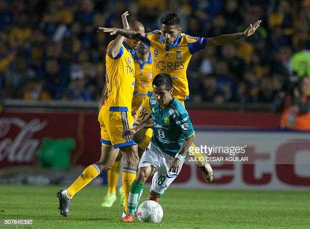 Javier Aquino of Tigres vies for the ball with Maximo Moralez of Leon during their Mexican Clausura 2016 tournament football match at the...