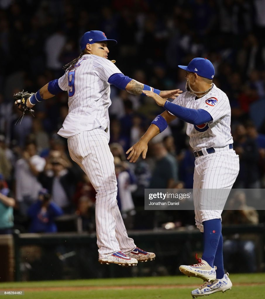 Javier Baez #9 and Jon Jay #30 of the Chicago Cubs celebrate a win over the New York Mets at Wrigley Field on September 12, 2017 in Chicago, Illinois. The Cubs defeated the Mets 8-3.