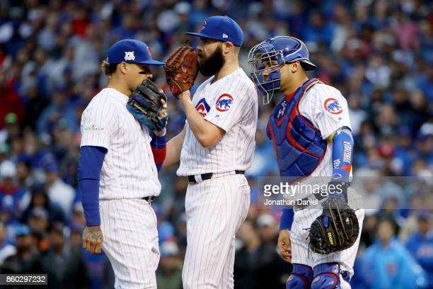 Javier Baez Jake Arrieta and Willson Contreras of the Chicago Cubs meet in the third inning during game four of the National League Division Series...