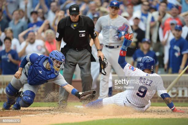 Javier Baez of the Chicago Cubs beats a tag at home plate by Raffy Lopez of the Toronto Blue Jays to score the winning run during the tenth inning at...