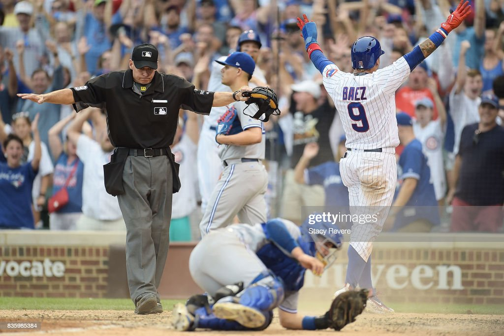 Javier Baez #9 of the Chicago Cubs beats a tag at home plate by Raffy Lopez #1 of the Toronto Blue Jays to score the winning run during the tenth inning at Wrigley Field on August 20, 2017 in Chicago, Illinois.