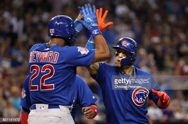 Javier Baez of the Chicago Cubs high fives Jason Heyward after hitting a three run home run against the Arizona Diamondbacks during the eighth inning...