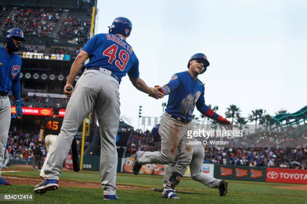 Javier Baez of the Chicago Cubs is congratulated by Jake Arrieta after hitting a two run inside the park home run against the San Francisco Giants...