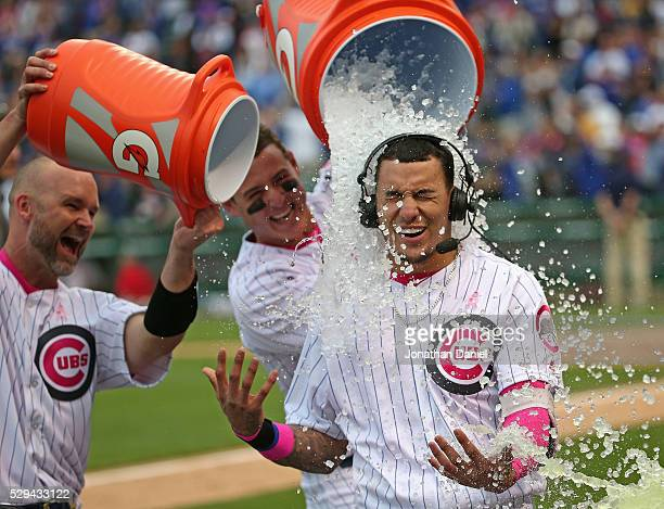 Javier Baez of the Chicago Cubs is doused with water by David Ross and Anthony Rizzo after hitting a gamewinning walk off home run against the...