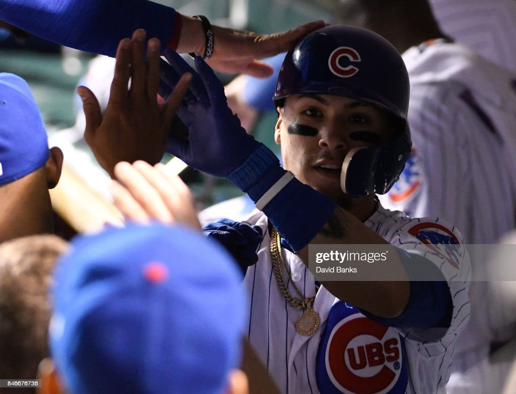 Javier Baez #9 of the Chicago Cubs is greeted by his teammates after hitting a home run against the New York Mets during the seventh inning on September 13, 2017 at Wrigley Field in Chicago, Illinois.