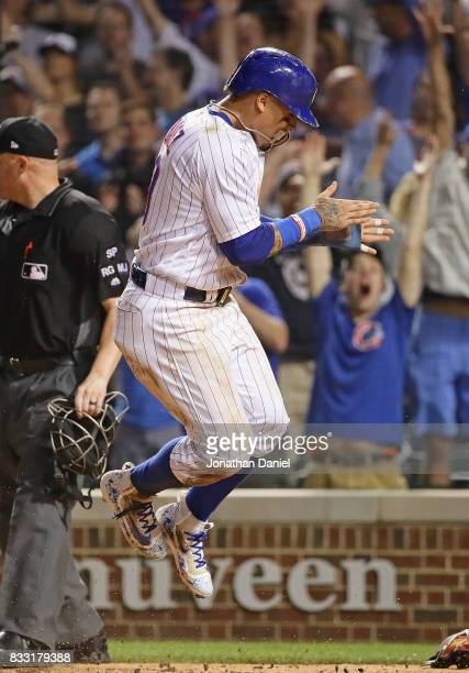 Javier Baez of the Chicago Cubs leaps in celebration after scoring the winning run on a wild pitch in the bottom of the 9th inning against the...