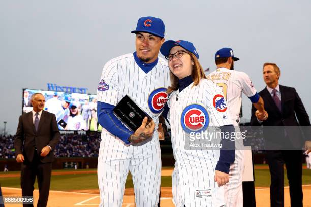 Javier Baez of the Chicago Cubs receives his ring from a fan during the World Series ring ceremony ahead of the game between the Los Angeles Dodgers...