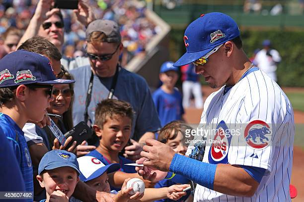 Javier Baez of the Chicago Cubs signs autographs before a game against the Tampa Bay Rays at Wrigley Field on August 9 2014 in Chicago Illinois The...