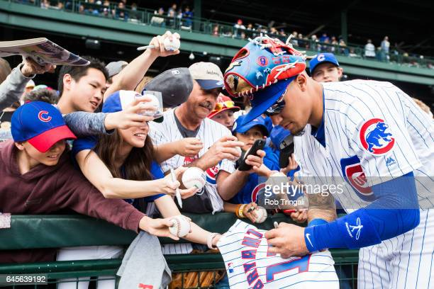 Javier Baez of the Chicago Cubs signs autographs before the spring training game against the Cleveland Indians during a spring training game at Sloan...
