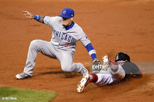 Javier Baez of the Chicago Cubs tags out Francisco Lindor of the Cleveland Indians as he attempts to steal second base during the third inning in...