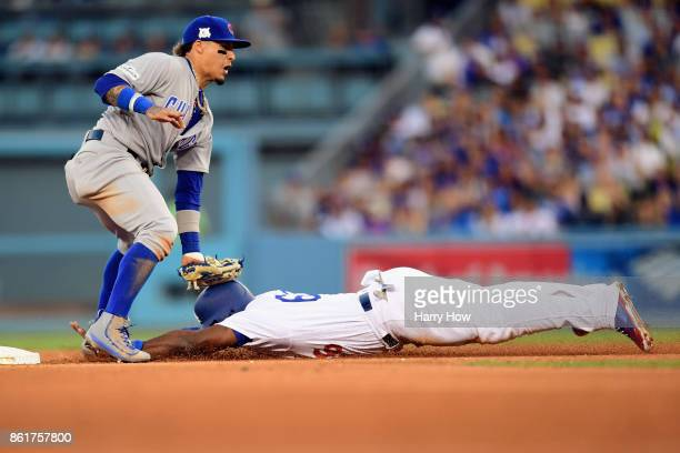 Javier Baez of the Chicago Cubs tags out Yasiel Puig of the Los Angeles Dodgers as he attempts to steal second base in the fourth inning during game...