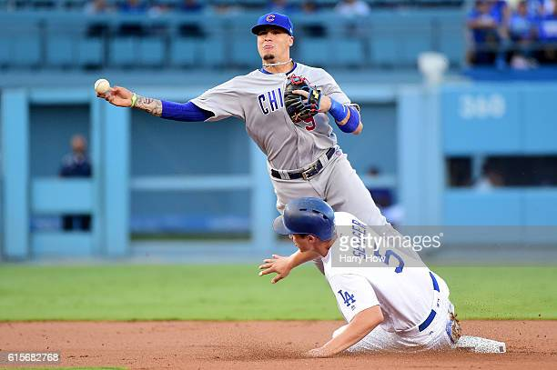 Javier Baez of the Chicago Cubs throws the ball to first base as Corey Seager of the Los Angeles Dodgers is out at second base in the first inning in...