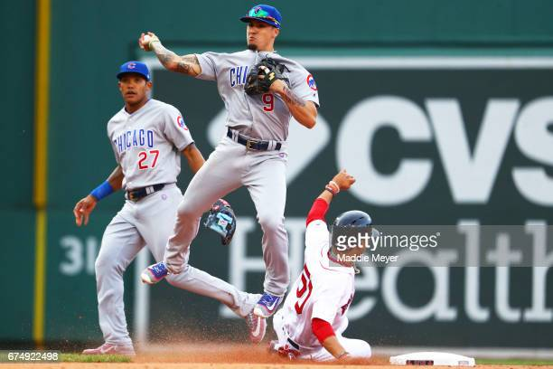 Javier Baez of the Chicago Cubs throws to first after tagging out Mookie Betts of the Boston Red Sox at second during the eighth inning at Fenway...