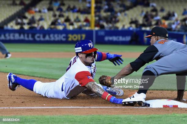 Javier Baez of the Puerto Rico is safe as he beats the tag by Xander Bogaerts of the Netherlands in the during Game 1 of the Championship Round of...
