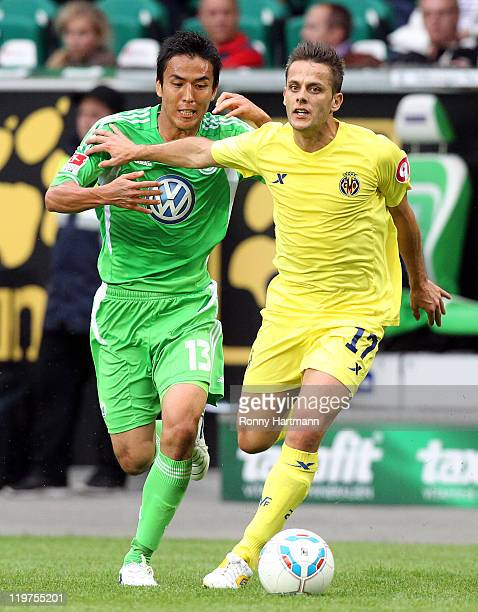 Javier Camunas of Villarreal of Wolfsburg is challenged by Makoto Hasebe of Wolfsburg during the preseason friendly between VfL Wolfsburg and...