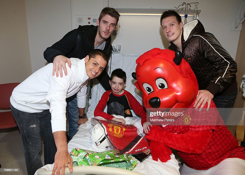 Javier 'Chicharito' Hernandez, David de Gea, Mascot Fred The Red and Phil Jones of Manchester United give presents to Ben O'Shea, 11, from Prestwich, as part of the Manchester United Foundation annual Christmas hospital visits at the Royal Manchester Children's Hospital on December 20, 2012 in Manchester, England.