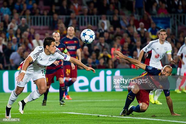 Javier 'Chicharito' Hernandez of Bayer 04 Leverkusen and Javier Mascherano of FC Barcelona compete for the ball during the UEFA Champions League...