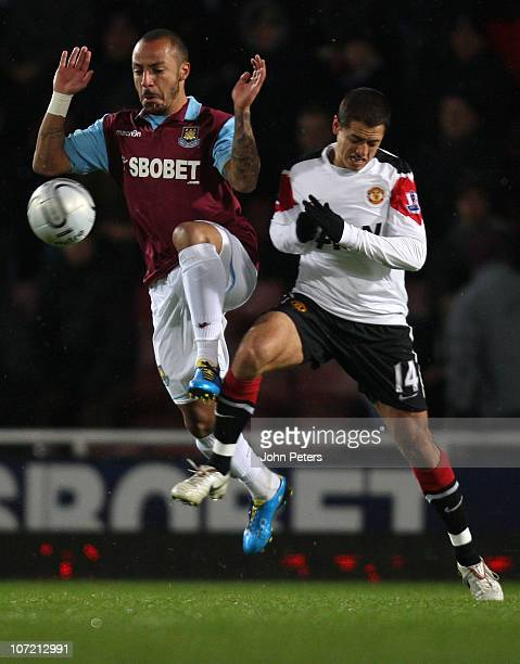 Javier 'Chicharito' Hernandez of Manchester United clashes with Julien Faubert of West Ham United during the Carling Cup quarterfinal match between...