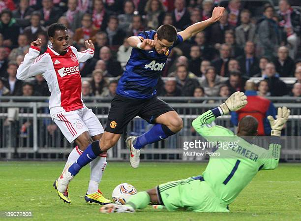 Javier 'Chicharito' Hernandez of Manchester United clashes with Vurnon Anita and Kenneth Vermeer of AFC Ajax during the UEFA Europa League round of...