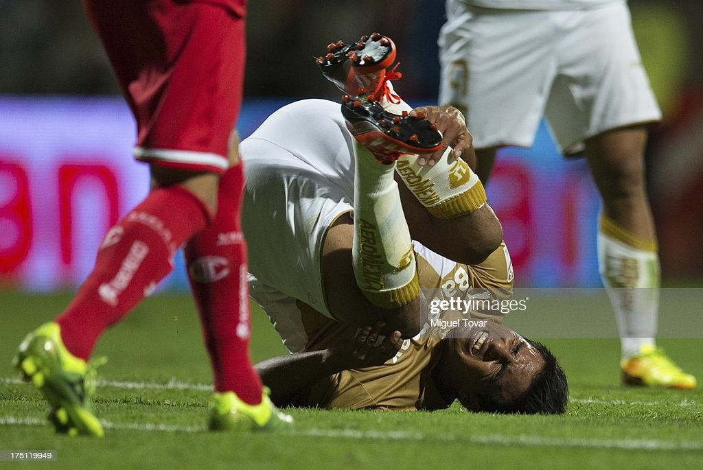 Javier Cortes grimaces in pain during a match between Toluca and Pumas as part of the Torneo Apertura 2013 Liga MX at Nemesio Siez stadium, on July 31, 2013 in Toluca, Mexico.