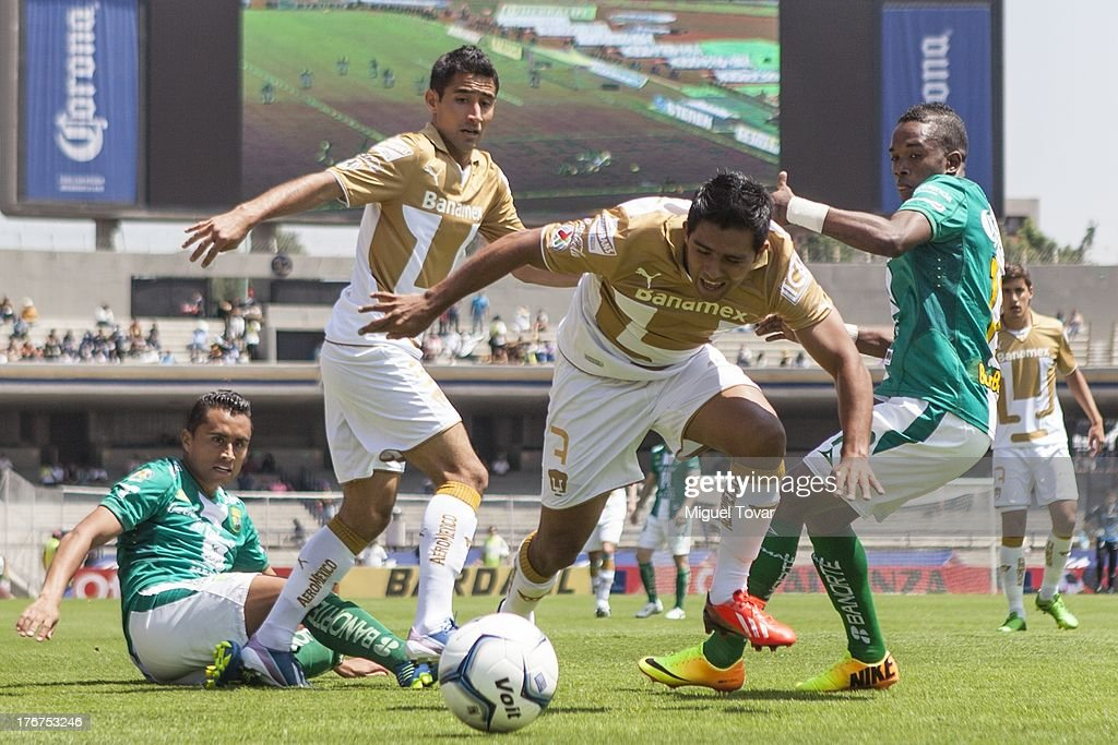 Javier Cortes of Pumas fights for the ball with Hernan Burbano of Leon during a match between Pumas and Leon as part of the Apertura 2013 Liga MX at Olympic stadium, on August 18, 2013 in Mexico City, Mexico.