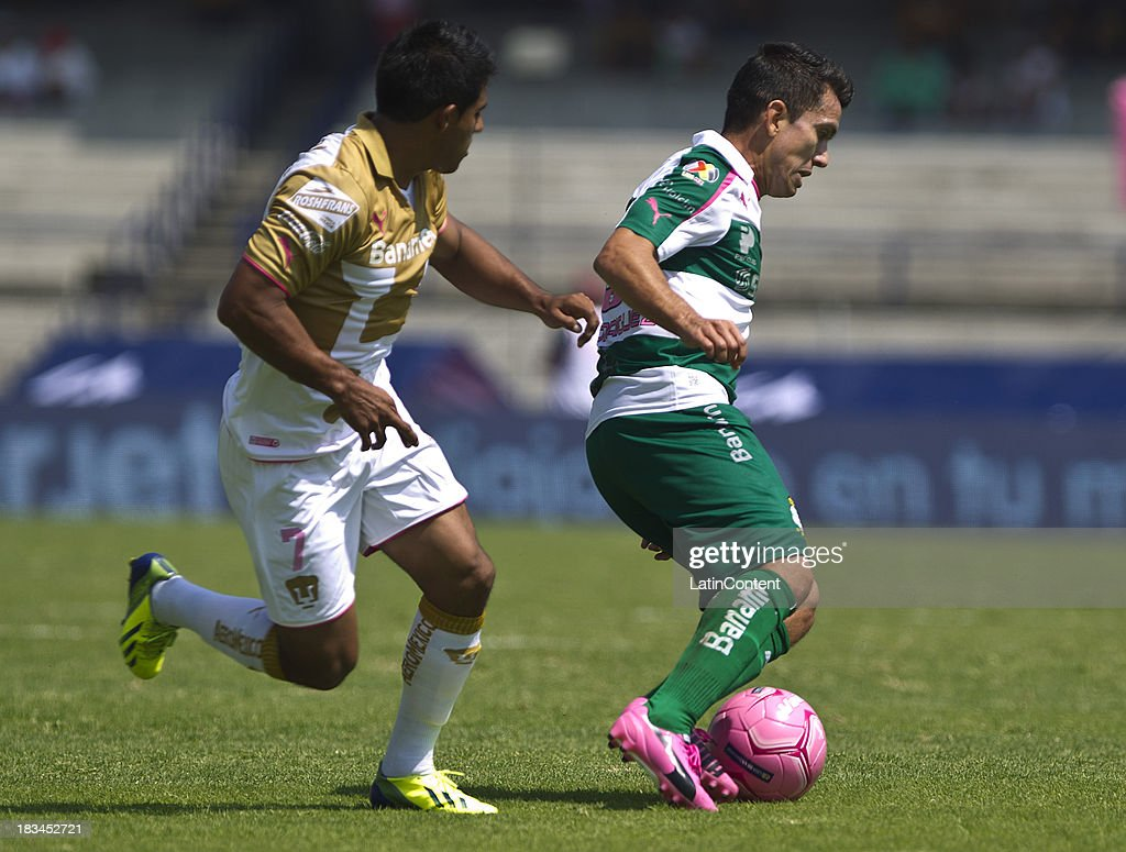 Javier Cortes (L) of Pumas fights for the ball with Juan Rodriguez (R) of Santos during a match between Pumas and Santos as part of the Apertura 2013 Liga MX at Olympic Stadium on October 06, 2013 in Mexico City, Mexico.