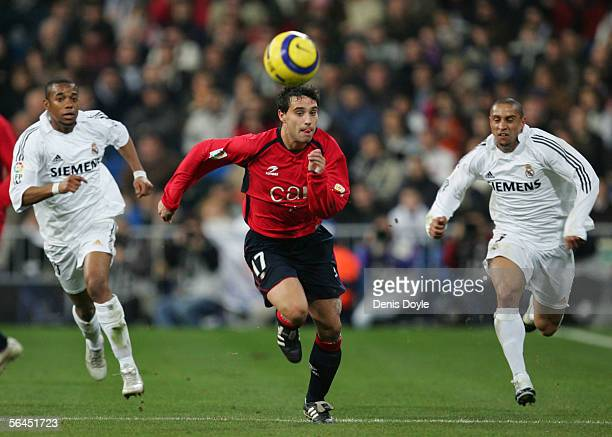 Javier Flano of Osasuna is chased by Robinho and Roberto Carlos of Real Madrid during a Primera Liga match between Real Madrid and Osasuna on...