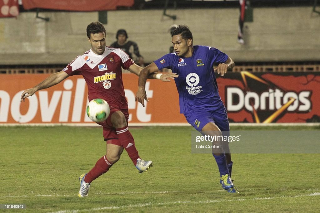 Javier Guarino of Caracas FC competes for the ball with Daniel Benitez of Deportivo La Guaira during a match between Caracas FC and Deportivo La Guaira as part of the Apertura 2013 at Brígido Iriarte Stadium on September 25, 2013 in Caracas, Venezuela.