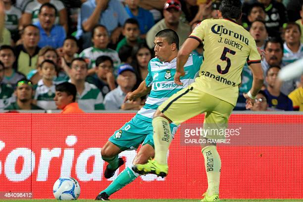 Javier Guemez of America vies for the ball with Luis Mendoza of Santos during their Mexican Apertura 2015 tournament football match at the TSM Corona...