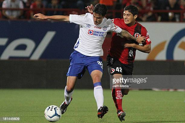 Javier Guemez of Tijuana struggles for the ball with Mauro Formica of Cruz Azul during the Apertura 2013 Liga Bancomer MX at Caliente Stadium on...