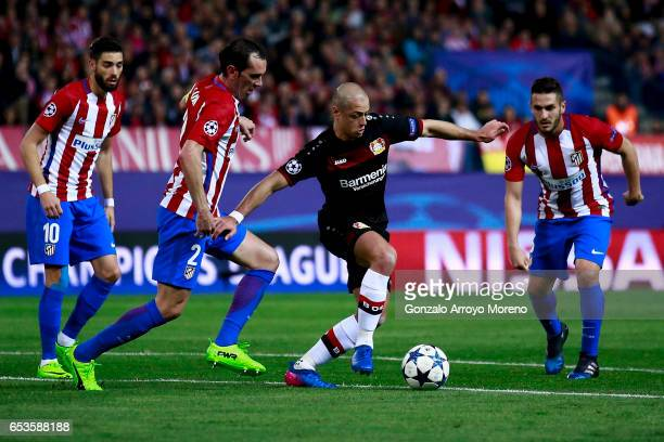 Javier Hernandez alias Chicharito of Bayer Leverkusen competes for the ball with Diego Godin Koke and Yannick Carrasco of Atletico de Madrid during...