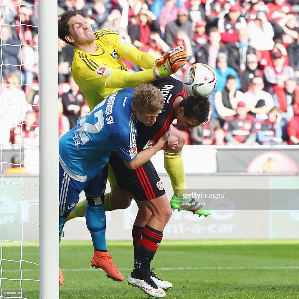 Javier Hernandez of Leverkusen is challenged by goalkeeper Rene Adler and Matthias Ostrzolek of Hamburg during the Bundesliga match between Bayer 04...
