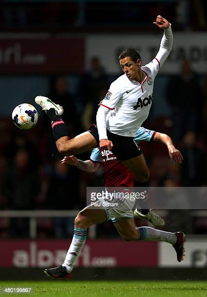 Javier Hernandez of Manchester United competes for the ball with George McCartney of West Ham during the Barclays Premier League match between West...