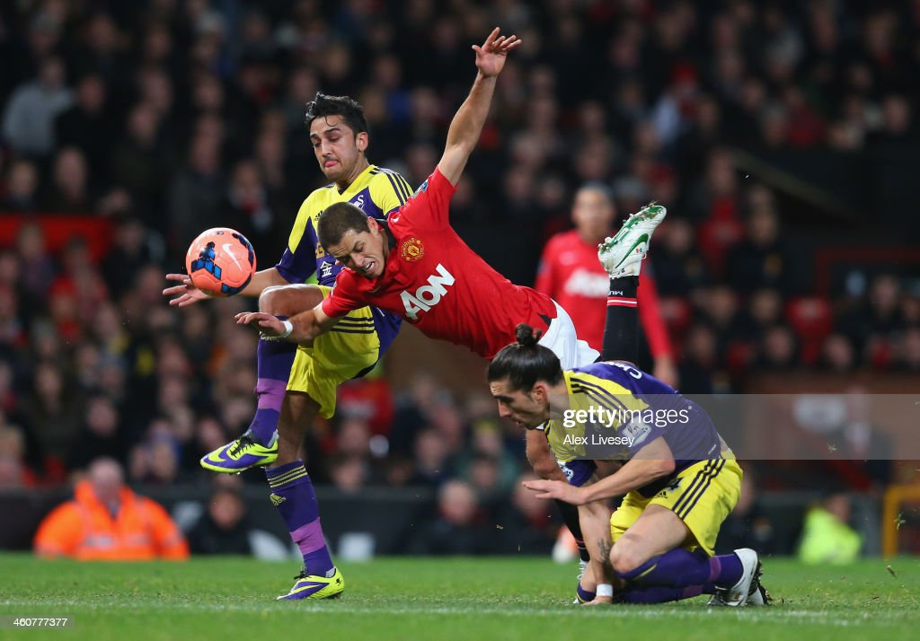 Javier Hernandez of Manchester United tangles with Neil Taylor and Chico Flores (R) of Swansea City during the FA Cup with Budweiser Third round match between Manchester United and Swansea City at Old Trafford on January 5, 2014 in Manchester, England.