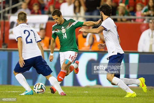 Javier Hernandez of Mexico hits a shot as Joao Moutinho and Luis Neto of Portugal try to defend it during the Internatinal friendly match between...
