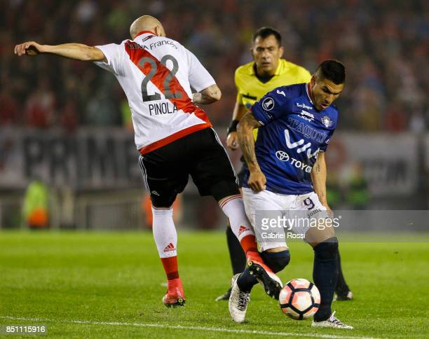 Javier Horacio Pinola of River Plate fights for the ball with Cristian Manuel Chavez of Wilstermann during a second leg match between River Plate and...
