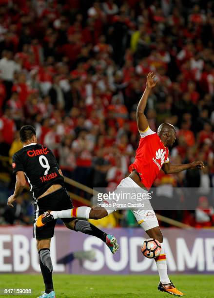 Javier Lopez of Santa Fe and Oscar Cardozo of Libertad compete for the ball during a second leg match between Independiente Santa Fe and Libertad as...