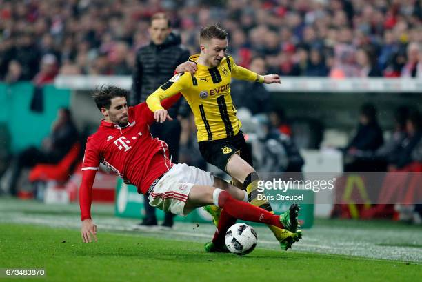 Javier Martinez of Muenchen and Marco Reus of Dortmund battle for the ball during the DFB Cup semi final match between FC Bayern Muenchen and...