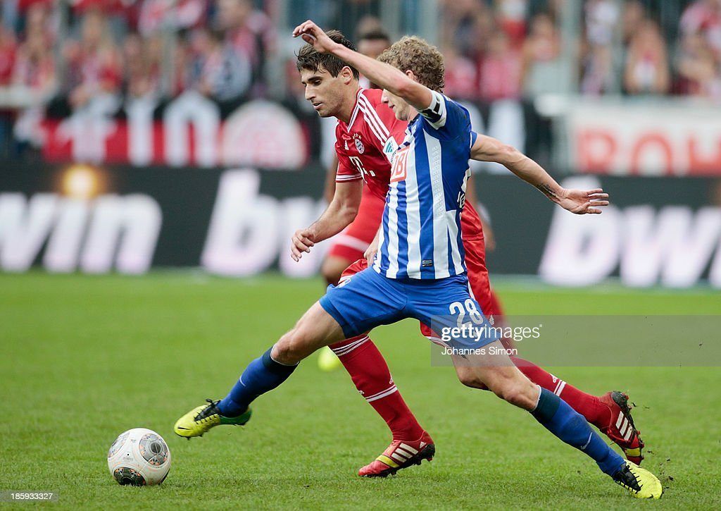 Javier Martinez (L) of Muenchen battles for the ball with Fabian Lustenberger of Berlin during the Bundesliga match between FC Bayern Muenchen and Hertha BSC Berlin at Allianz Arena at Allianz Arena on October 26, 2013 in Munich, Germany.