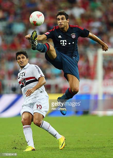 Javier Martinez of Muenchen is challenged by Aloisio of Sao Paulo during the Audi Cup match between FC Bayern Muenchen and FC Sao Paulo at Allianz...