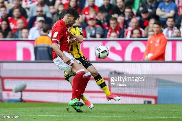 Javier Martinez of Munich and Christian Pulisic of Dortmund battle for the ball during the Bundesliga match between Bayern Muenchen and Borussia...