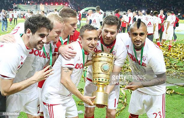 Javier Martinez Sebastian Rode Joshua Kimmich Rafinha Xabi Alonso and Arturo Vidal of Muenchen celebrate with the trophy after winning the DFB Cup...