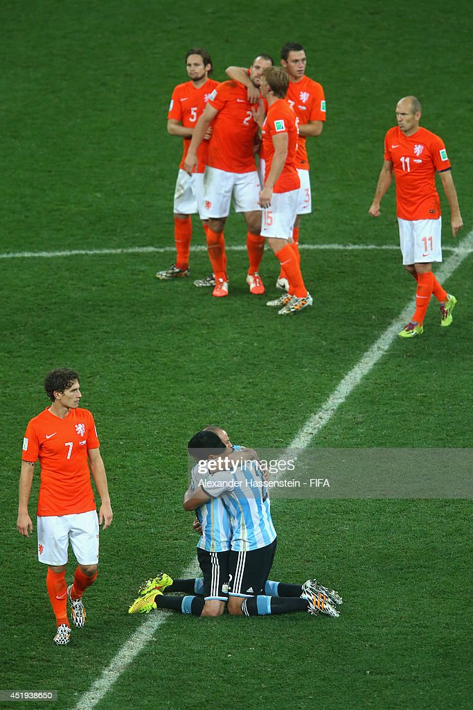 Javier Mascherano (C-L) of Argentina celebrates with his team mate Ezequiel Garay defeating the Netherlands in a shootout whilst Daryl Janmaat (front L) of Netherlands and his team mates Daley Blind (back L-R), Rob Vlaar, Dirk Kuyt, Stefan de Vrij and Arjen Robben reacts during the 2014 FIFA World Cup Brazil Semi Final match between the Netherlands and Argentina at Arena de Sao Paulo on July 9, 2014 in Sao Paulo, Brazil.