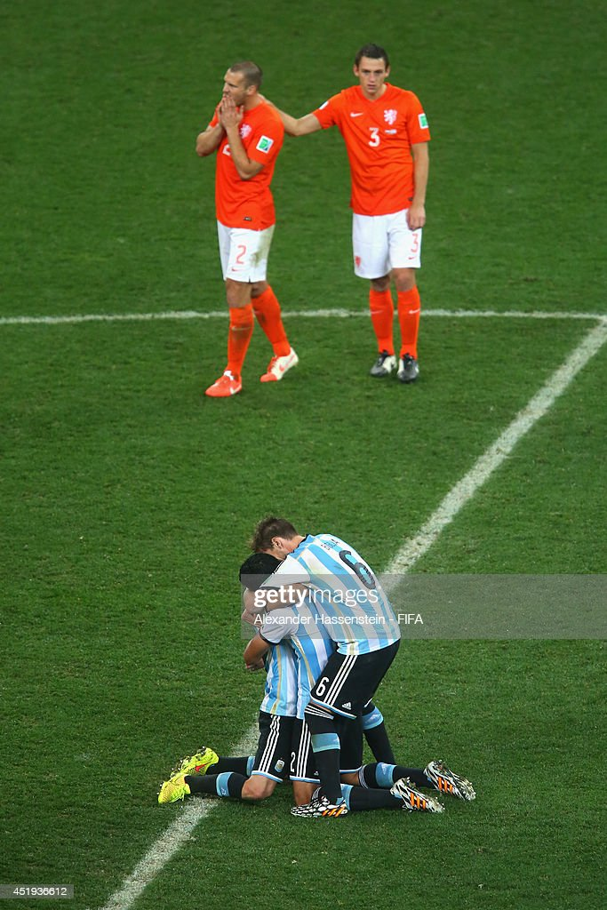 <a gi-track='captionPersonalityLinkClicked' href=/galleries/search?phrase=Javier+Mascherano&family=editorial&specificpeople=490876 ng-click='$event.stopPropagation()'>Javier Mascherano</a> (L) of Argentina celebrates with his team mates <a gi-track='captionPersonalityLinkClicked' href=/galleries/search?phrase=Ezequiel+Garay&family=editorial&specificpeople=857797 ng-click='$event.stopPropagation()'>Ezequiel Garay</a> and Lucas Biglia defeating the Netherlands in a shootout whilst <a gi-track='captionPersonalityLinkClicked' href=/galleries/search?phrase=Ron+Vlaar&family=editorial&specificpeople=605352 ng-click='$event.stopPropagation()'>Ron Vlaar</a> (back - L) of Netherlands and his team mate Stefan de Vrij reacts during the 2014 FIFA World Cup Brazil Semi Final match between the Netherlands and Argentina at Arena de Sao Paulo on July 9, 2014 in Sao Paulo, Brazil.
