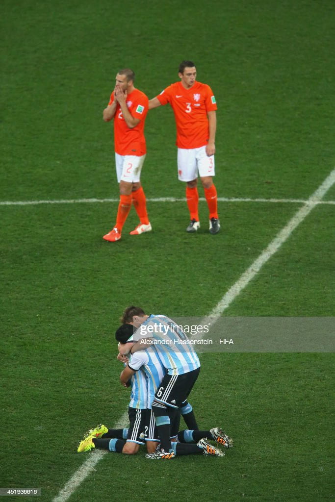 Javier Mascherano (L) of Argentina celebrates with his team mates Ezequiel Garay and Lucas Biglia defeating the Netherlands in a shootout whilst Ron Vlaar (back - L) of Netherlands and his team mate Stefan de Vrij reacts during the 2014 FIFA World Cup Brazil Semi Final match between the Netherlands and Argentina at Arena de Sao Paulo on July 9, 2014 in Sao Paulo, Brazil.