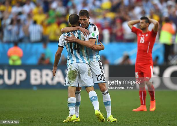 Javier Mascherano of Argentina celebrates with Jose Maria Basanta of Argentina as Blerim Dzemaili of Switzerland looks on after the 2014 FIFA World...