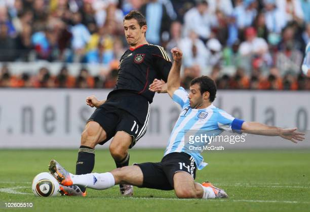 Javier Mascherano of Argentina tackles Miroslav Klose of Germany during the 2010 FIFA World Cup South Africa Quarter Final match between Argentina...