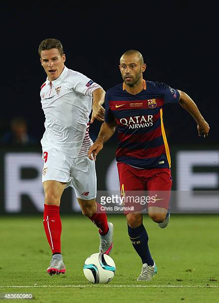 Javier Mascherano of Barcelona holds off Kevin Gameiro of Sevilla during the UEFA Super Cup between Barcelona and Sevilla FC at Dinamo Arena on...
