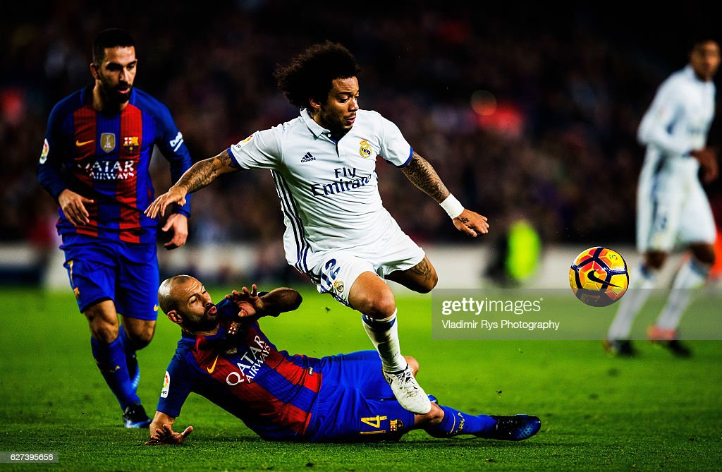 Javier Mascherano of Barcelona slides into Marcelo of Real Madrid during the La Liga match between FC Barcelona and Real Madrid CF at Camp Nou...