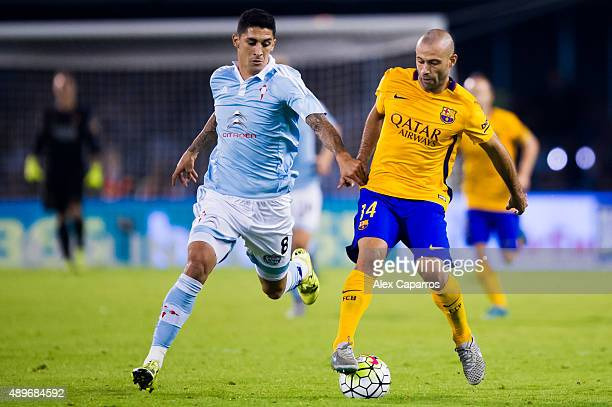 Javier Mascherano of FC Barcelona conducts the ball next to Pablo Hernandez of Celta Vigo during the La Liga match between Celta Vigo and FC...